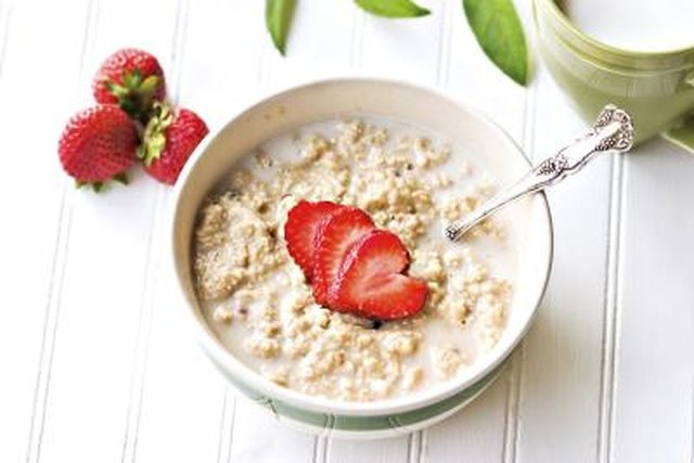A bowl of oatmeal with strawberries.
