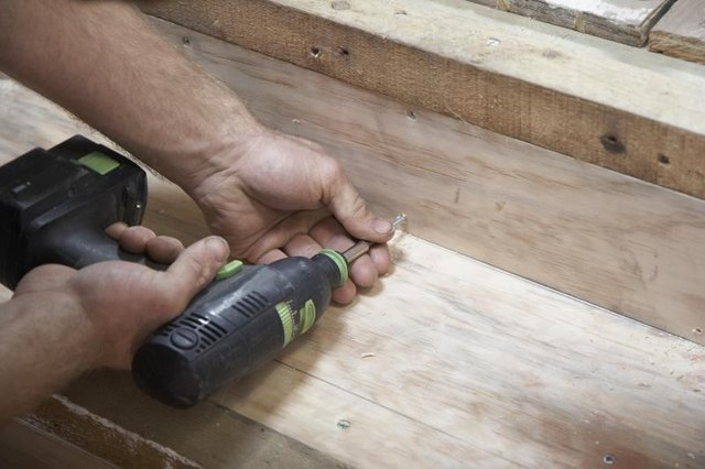 A carpenter is using a cordless drill to make a staircase.