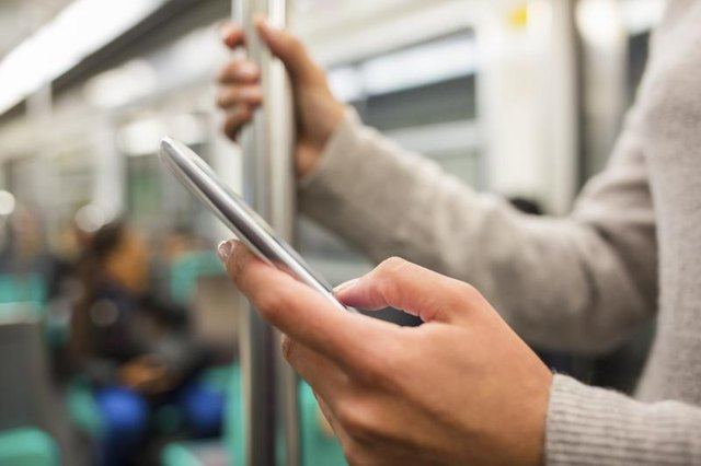 Woman's hands using a smartphone on the subway.