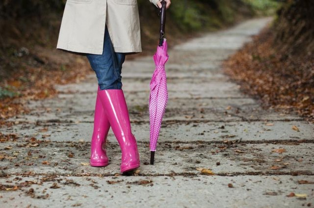 Woman wearing pink rainboots and holding a pink umbrella.