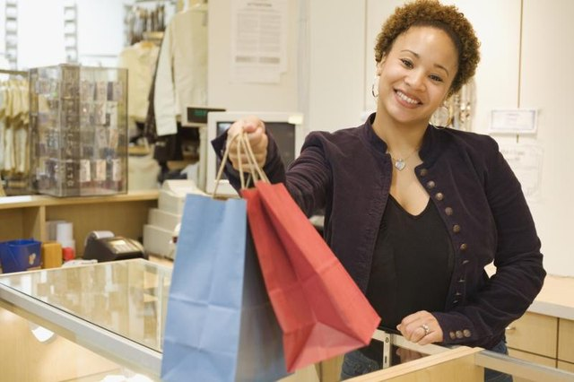 A cashier at a boutique store handing over bags.