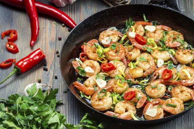 Grilled shrimp with herbs in a pan.