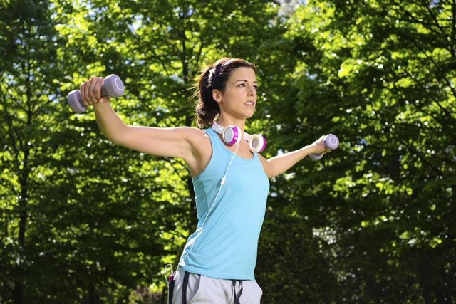 A woman outside performing shoulder exercises.