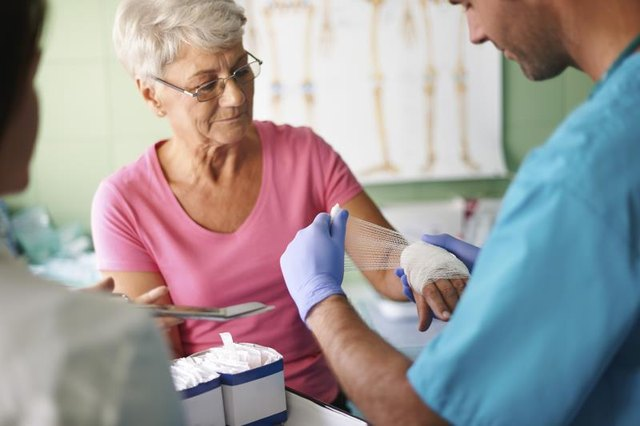 A medical assistant bandages an elderly patient's hand