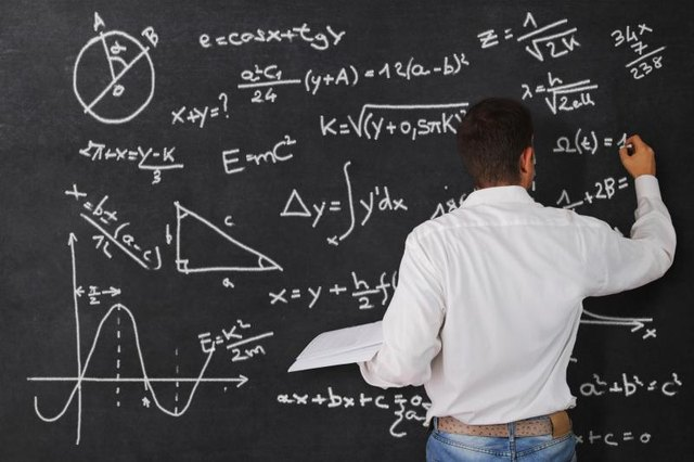 A man writes signs and symbols in mathematics on a chalkboard.