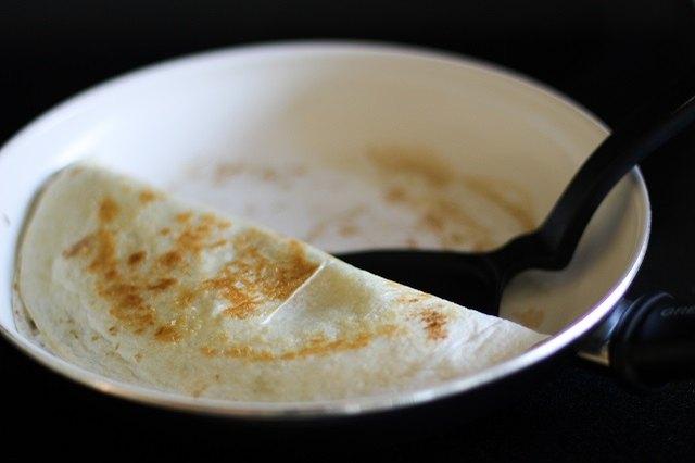 Carefully flip the folded quesadilla.