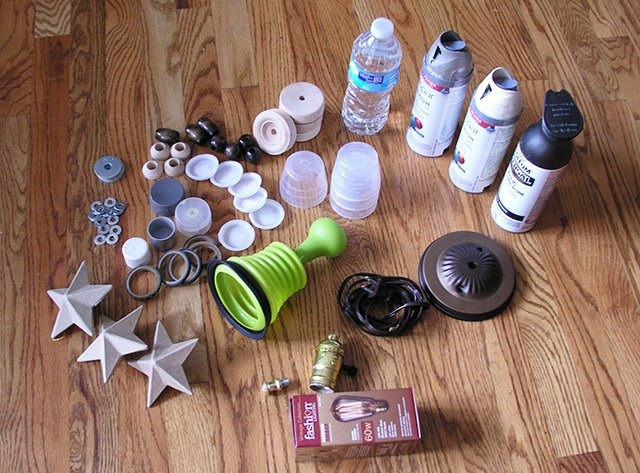 Cans of spray paint, lamp kit, wooden beads, plastic lids and sink plunger
