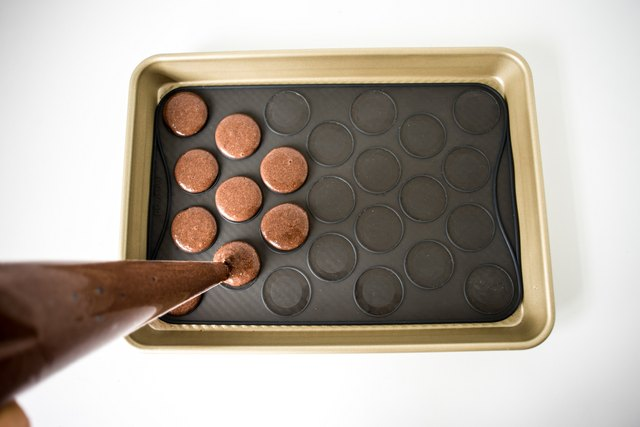 Pipe the macarons onto the baking parchment or silicone macaron slip-mat.
