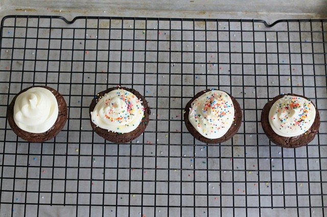 Cupcakes with sprinkles on a wire rack.
