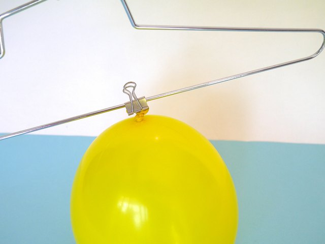 Clip the balloon to the wire hanger.