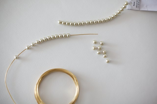 String pearl beads onto wire.