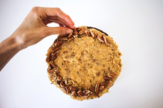 Decorate the top of the cake with pecans and chocolate shavings.