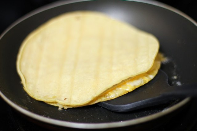 Flip the quesadilla carefully with a spatula.