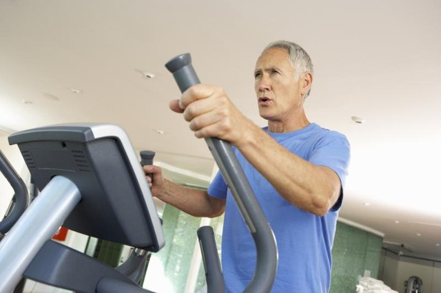 A mature man is using the elliptical machine at the gym.