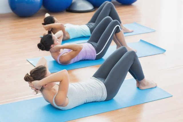 Three women doing crunches on mats in a studio.