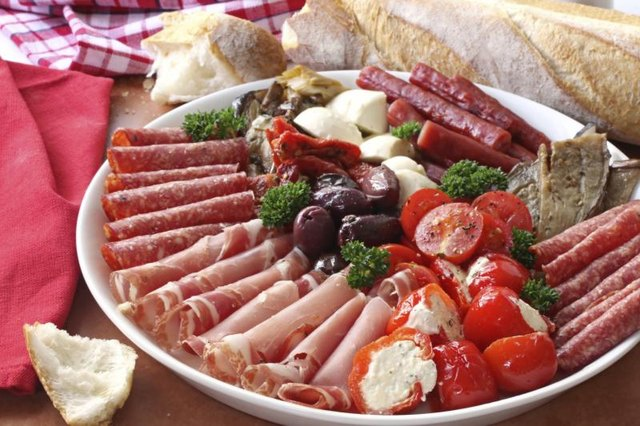 Antipasto platter with meats, cheeses, and breads on table.