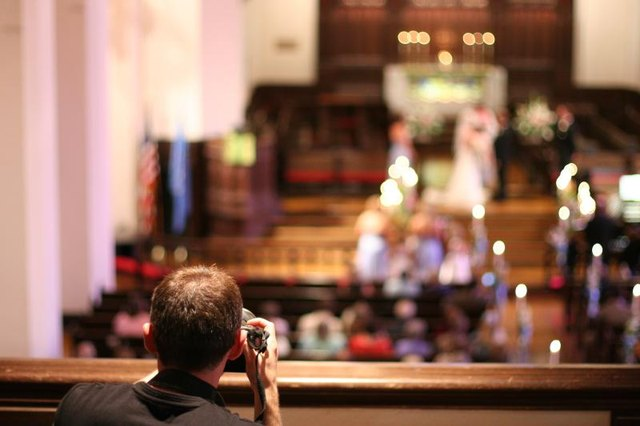 Photographer sets up shot from the balcony of a church