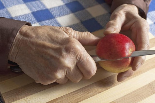 A close-up of a woman with arthritic hands slicing an apple.