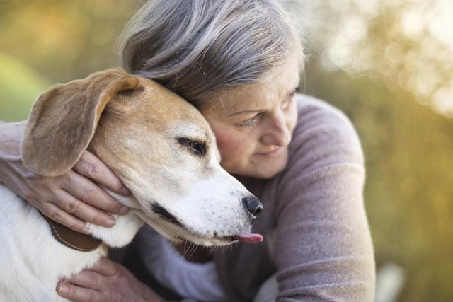 An older woman with a dog.