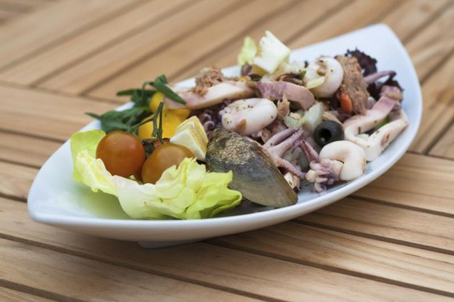 Mussels, squid and other seafood tossed on a platter with fresh vegetables, black olives and lemon.