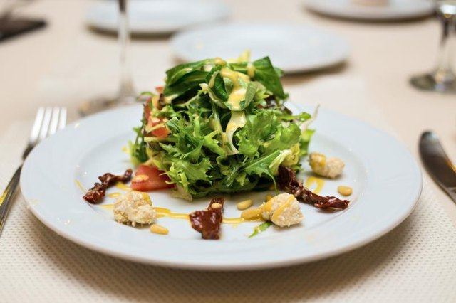 A plate of spinach salad served with goat cheese and pine nuts.