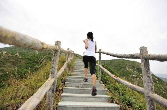 A woman jogging up a flight of stairs in a natural outdoor setting.