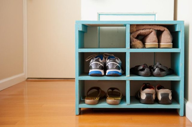 Shoes stored on shelves in a mudroom.