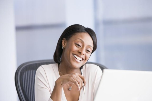 Woman smiling at a laptop