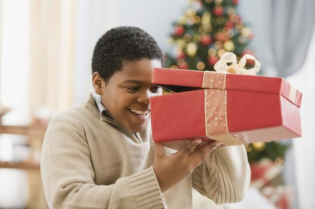 Young boy peeking into a box in front of a Christmas tree.