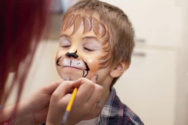 Young boy having lion faceprint applied.