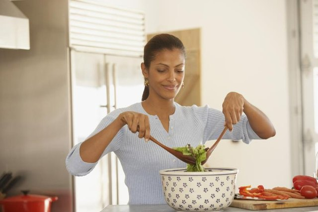 A woman tossing salad in her kitchen.
