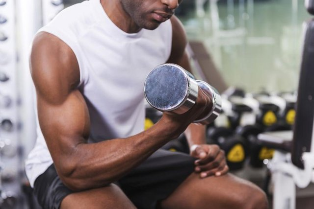 A man does bicep curls at a gym.