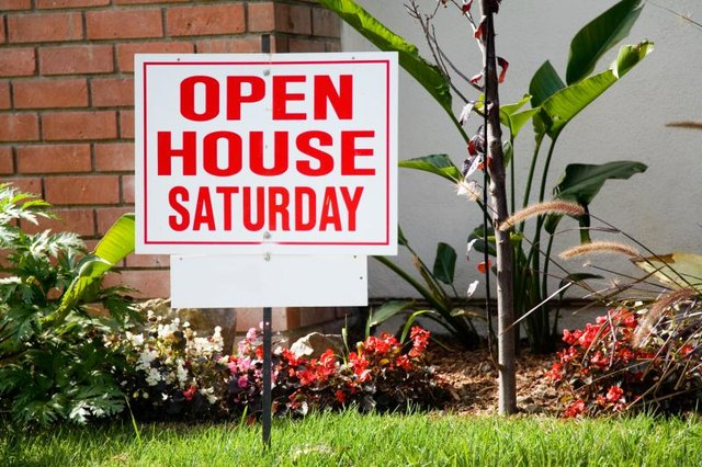An open house sign in front of a house.