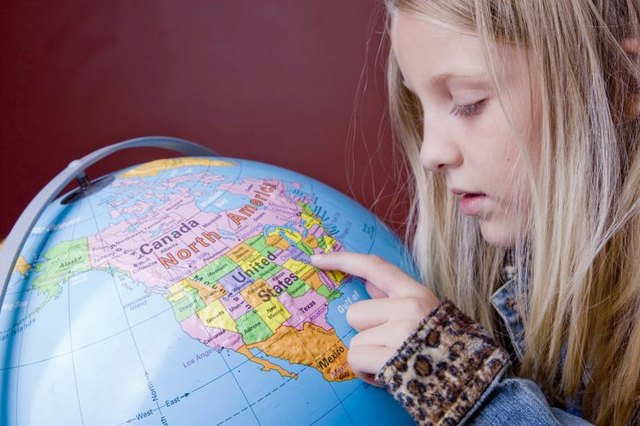A young student is looking at a globe.