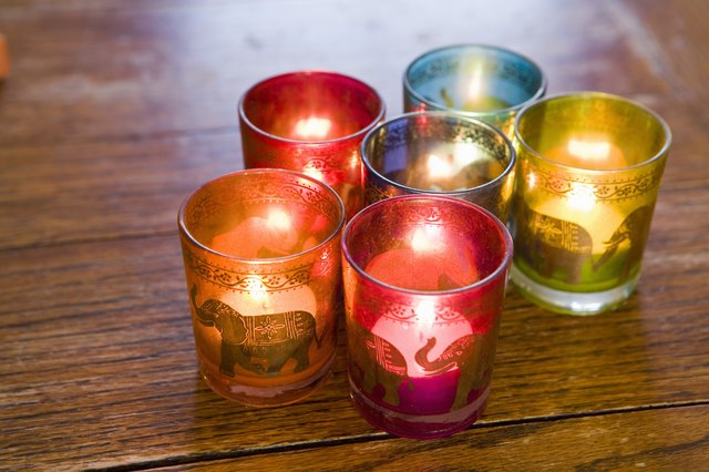 Candles in colorful glass holders on a table.