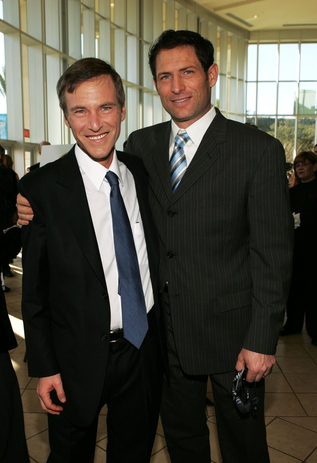 A former NFL quarterback poses for a photo with a sports agent.