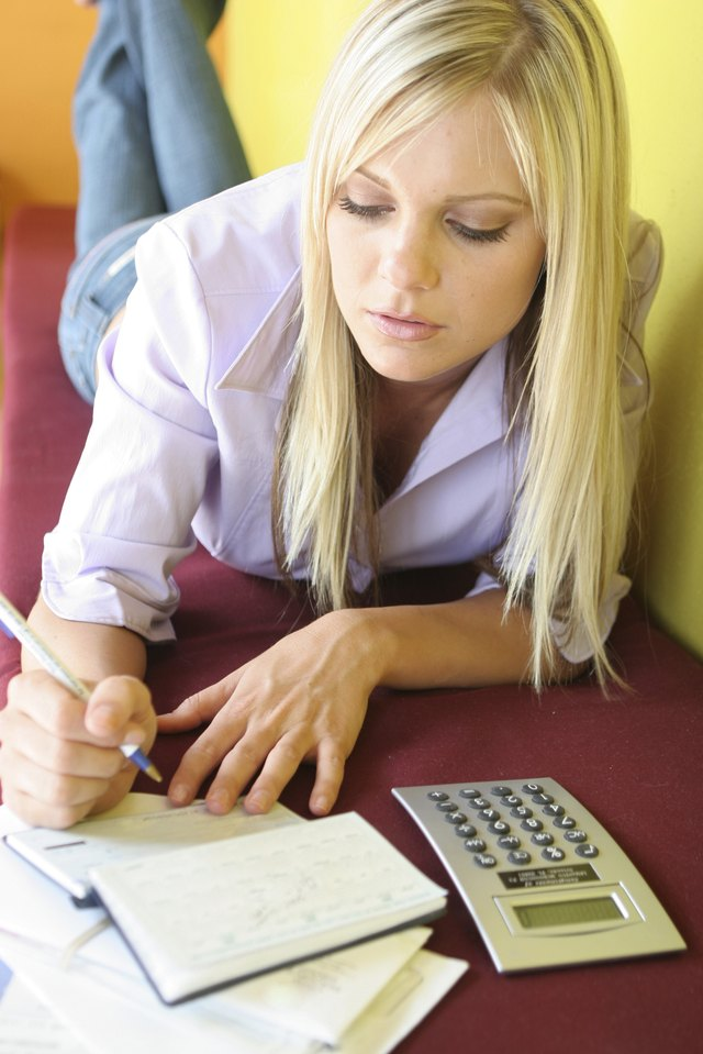 Close-up of woman filling out personal check.