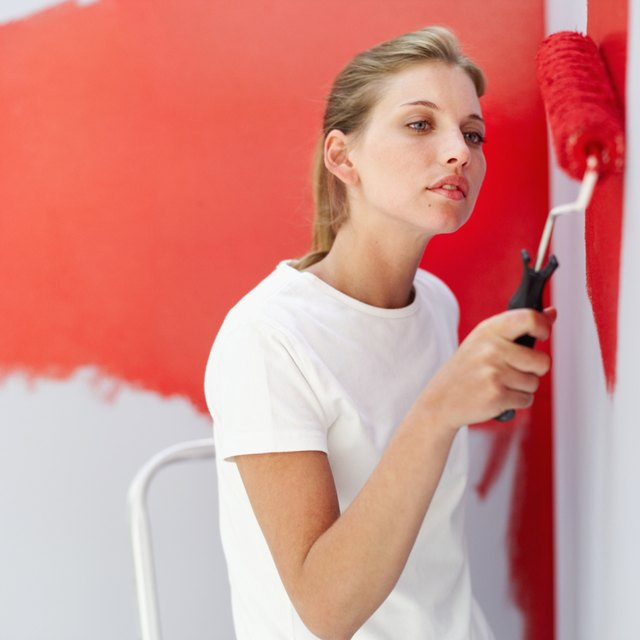 Close-up of woman painting a wall red.