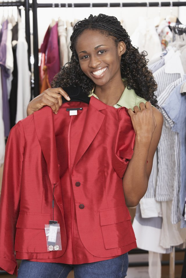 A woman is holding a red jacket in front of her.