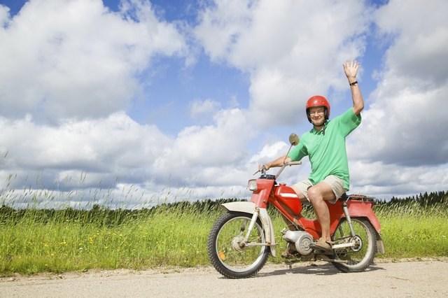 A man waves while riding a moped on a country road.