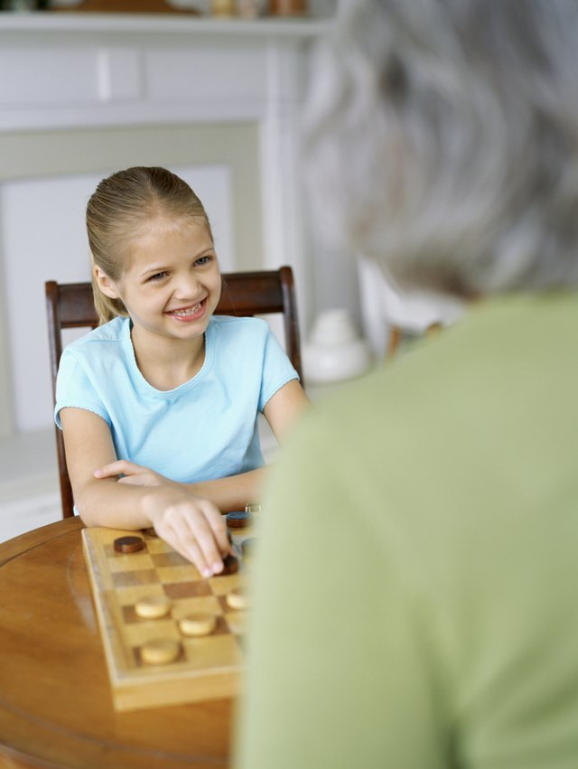 Little girl playing checkers with grandmother
