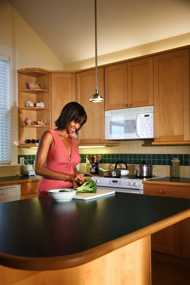Woman cutting broccoli in the kitchen