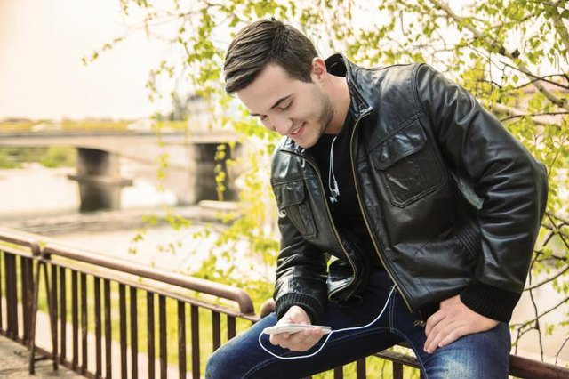 Young man weating a leather jacket, using a smartphone