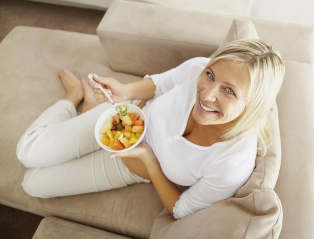 A woman reclines while eating a bowl of fruit on an ultra suede couch.