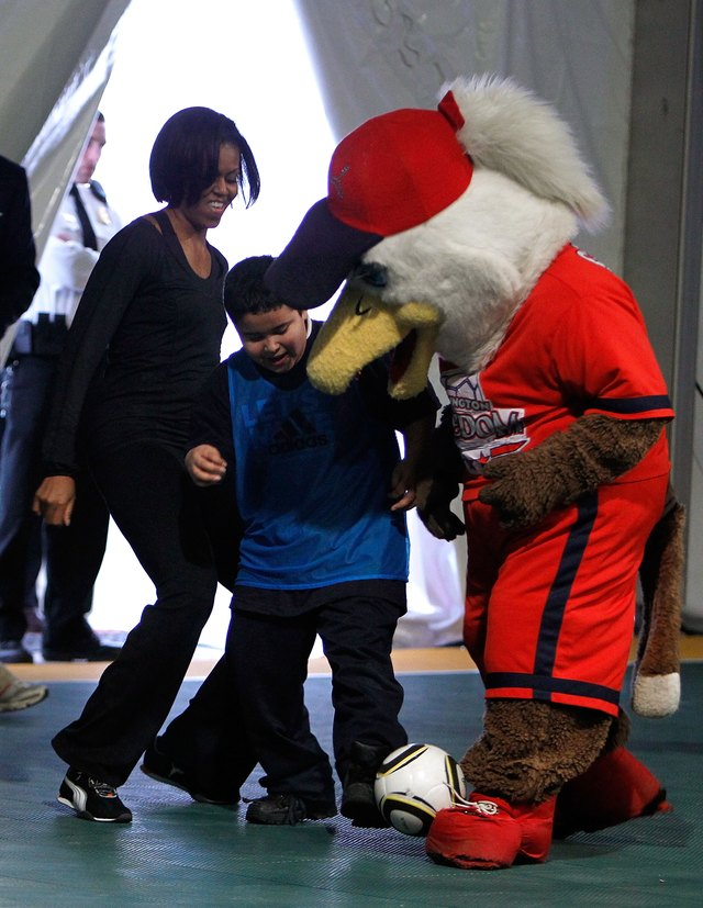 First Lady Michelle Obama, student and Eagle mascot kick soccer ball around