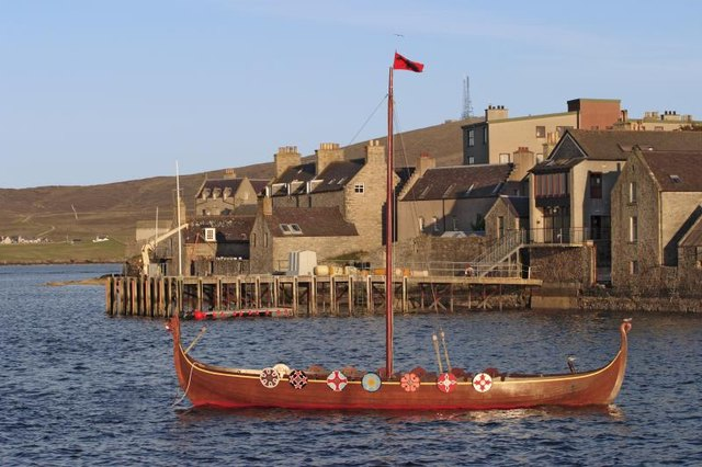A viking boat in a small harbour.