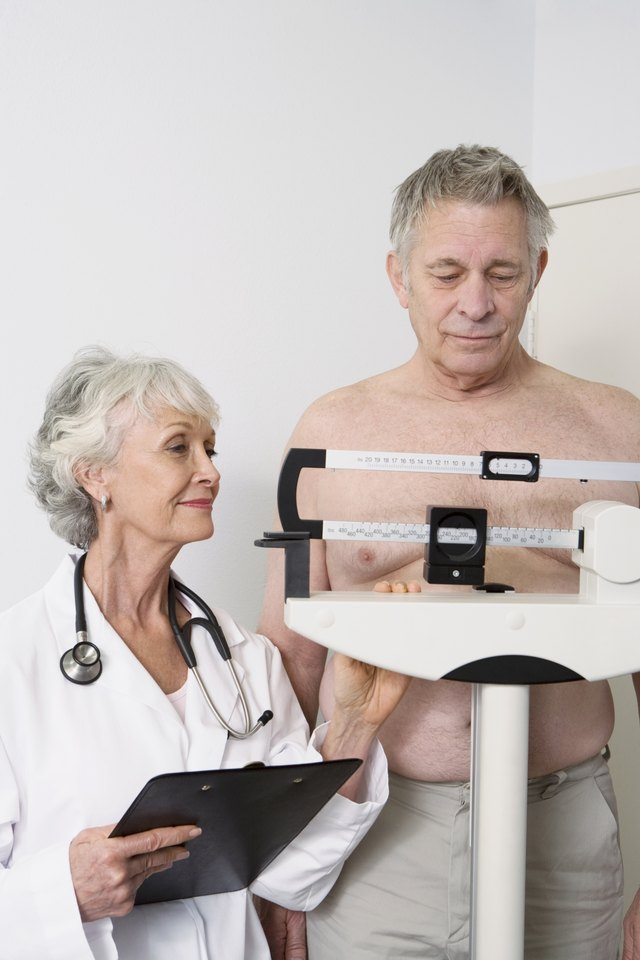 Senior man gets weighed by doctor