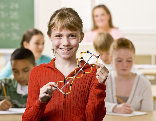 A smiling student holding a double helix model in a crowded classroom.
