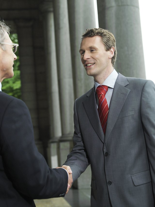 Man shaking hands in a gray suit