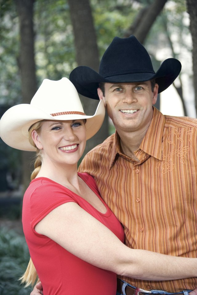 Smiling couple wearing cowboy hats.